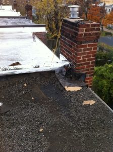 Two layers of roofing on this flat roof row house.