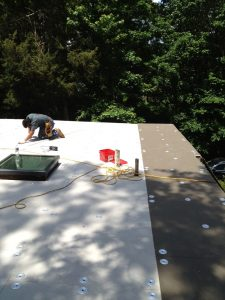 Installing new flat roof insulation board.