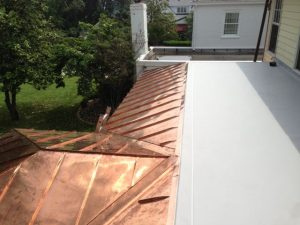 Gray TPO roof above new standing seam copper roof